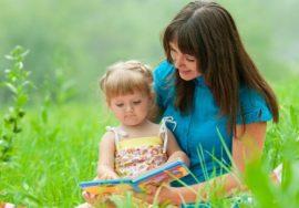Мама с маленькой дочкой читают книгу на природе