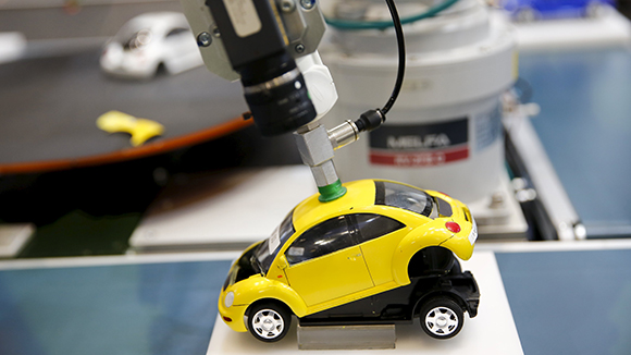 """A robotic arm by Mitsubishi Electric assembles a toy car at the System Control Fair SCF 2015 in Tokyo, Japan in this December 2, 2015 file photo. Japan is expected to release manufacturing PMI data this week. REUTERS/Thomas Peter/Files GLOBAL BUSINESS WEEK AHEAD PACKAGE - SEARCH """"BUSINESS WEEK AHEAD JANUARY 18"""" FOR ALL IMAGES"""